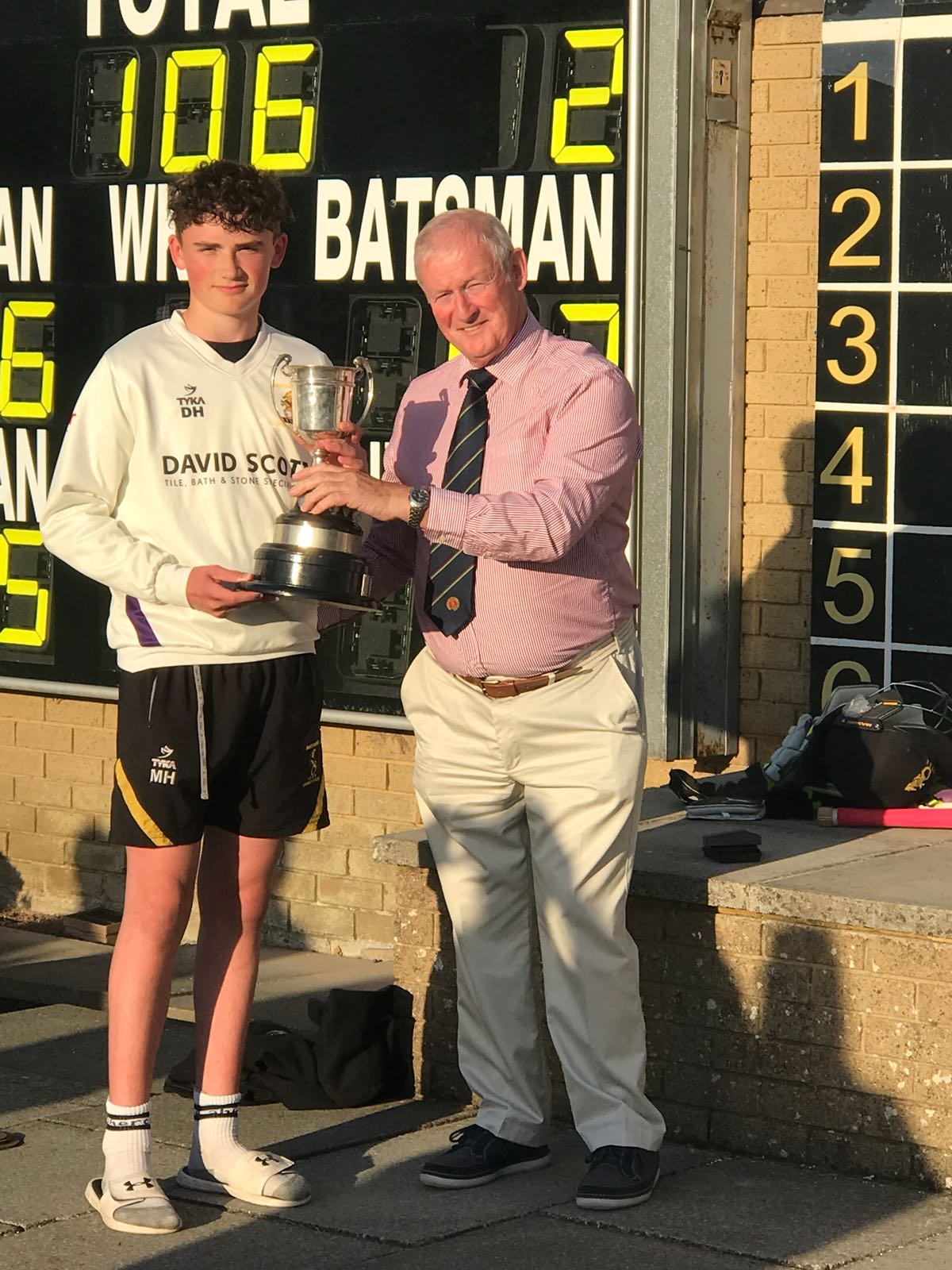 Instonians U 15 captain Matthew Humphreys receives the Graham Cup from NCU President Clarence Hiles